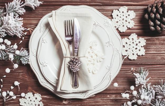 Table de service de noël dans un style shabby chic. vue de dessus, flocons de neige au crochet