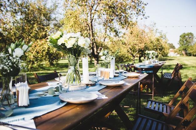 Table servie en bois sur fond de nature verdoyante. vase avec des fleurs.