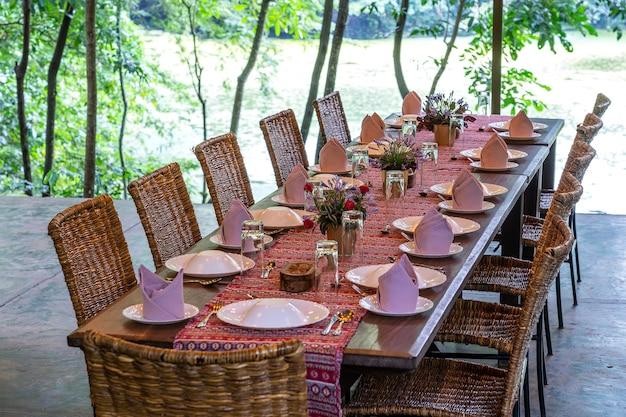 Table servie et chaises en rotin dans une terrasse de restaurant vide
