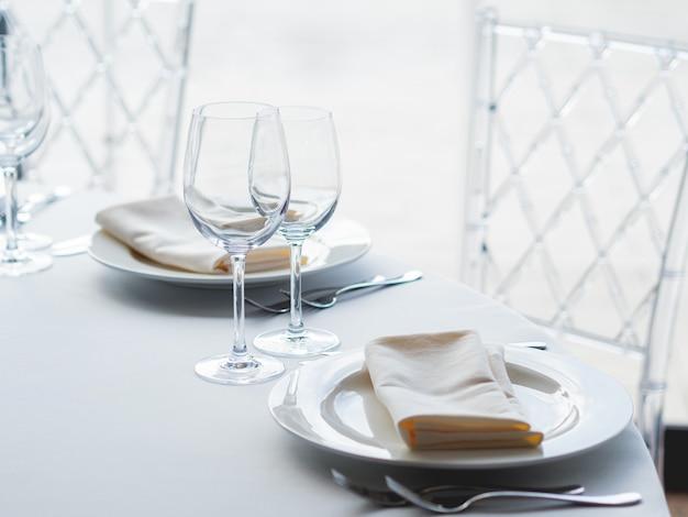 Table servie pour le banquet avec couverts, verres à vin et serviettes.
