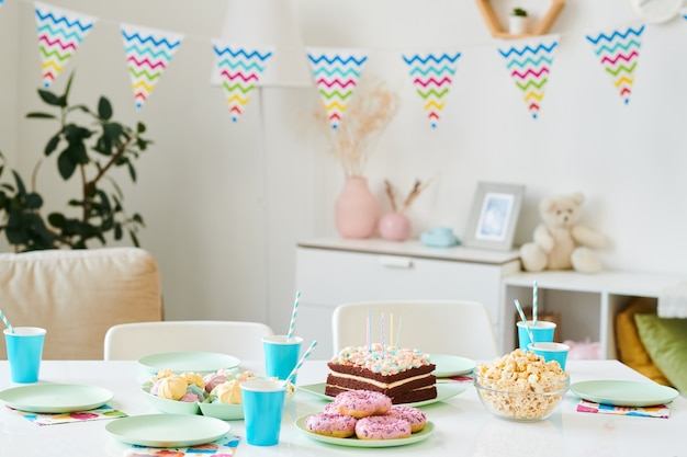 Table servie pour la fête d'anniversaire à domicile pour les enfants avec un gâteau avec des bougies, des boissons dans des verres en papier bleu, du maïs soufflé, des beignets et des merengues