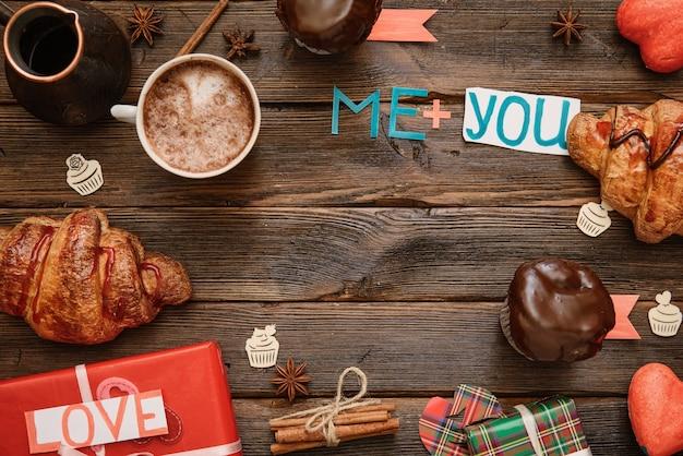 Table servie pour la saint-valentin avec une tasse de cappuccino, des desserts sucrés et des lettres faites à la main