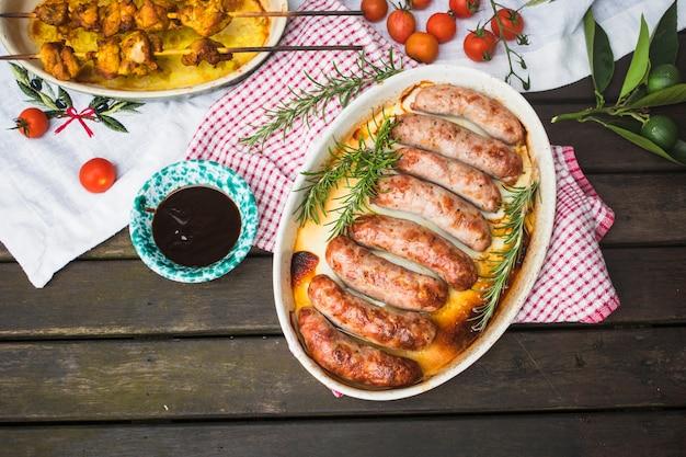 Table servie avec de la viande grillée et des saucisses