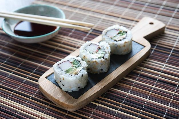 Table avec sushis avec baguettes et bol avec sauce soja