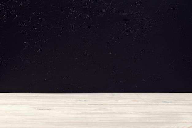 Table de table en bois blanc vide sur mur texturé noir