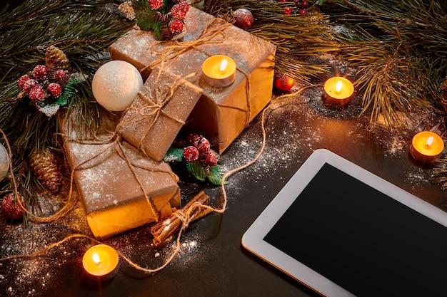 Table avec tablette, jouets de noël, étoiles et branches de sapin duveteuses. espace libre pour le texte. vue de dessus. espace de copie. fermer