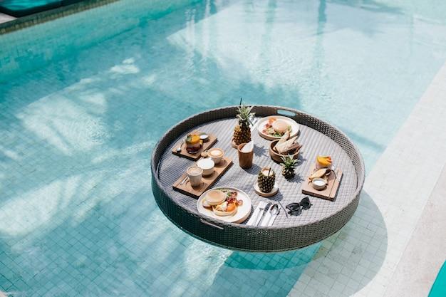 Table avec des tasses de cappuccino et des assiettes de fruits. déjeuner exotique en piscine.