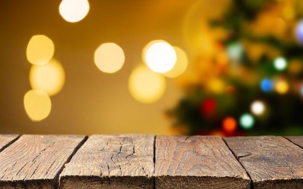 Table de terrasse en bois rustique vide de noël sur l'arbre de noël et flou de lumière floue. sapin avec boules et guirlande.