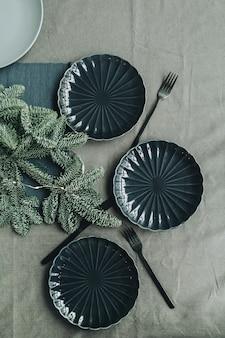 Table de thanksgiving de noël décorée de branches de sapin, guirlande, assiettes, couteaux, fourchettes