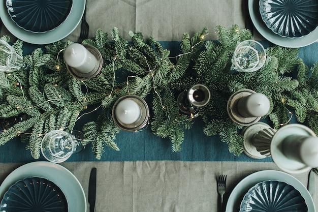Table de thanksgiving de noël décorée de branches de sapin, guirlande, bougies, assiettes, couteaux, fourchettes