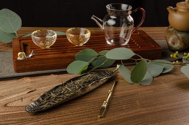 La table à thé avec instruments théières tasses crêpe et thé shen puer