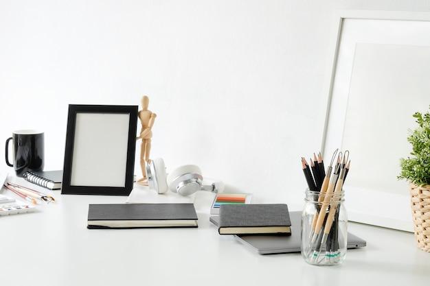 Table de travail de l'artiste avec crayon, carnet de croquis, cadre photo et décoration végétale.