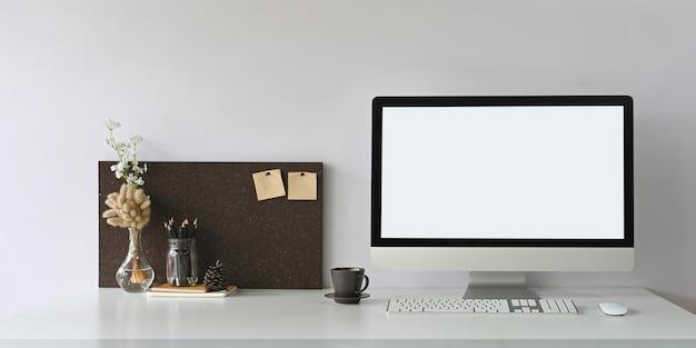 Une table de travail blanche est entourée d'un écran d'ordinateur blanc et d'un équipement de bureau