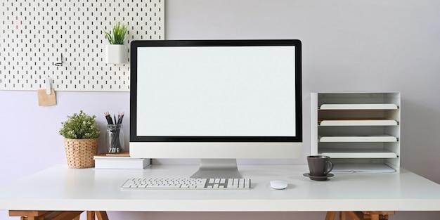 Une table de travail blanche est entourée d'un moniteur d'ordinateur à écran blanc et de divers équipements