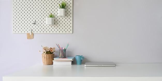 Une table de travail blanche est entourée d'un ordinateur portable et de divers équipements