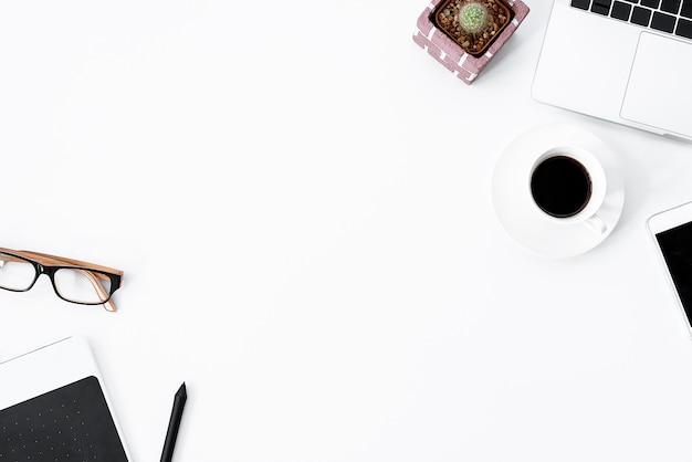 Table de travail blanche graphic designer avec ordinateur, cactus, café, téléphone et stylo