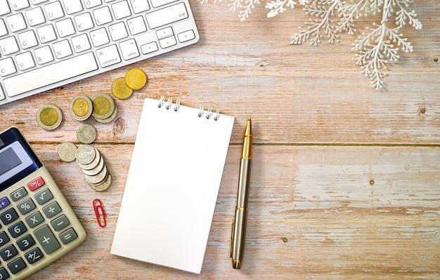 Table de travail en bois avec clavier d'ordinateur portable calculatrice de monnaie et concept de coût des fournitures