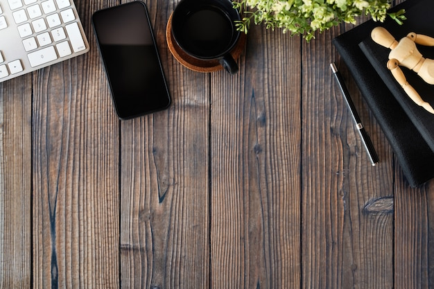 Table de travail en bois avec fournitures de bureau et espace de copie.