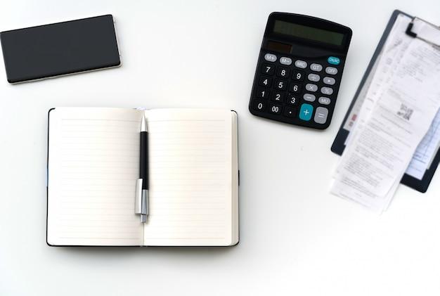 Table de travail de bureau avec facture, téléphone mobile, ordinateur portable et calculatrice sur tableau blanc, vue de dessus, espace de copie pour message texte
