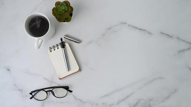 Table de travail avec cahier, tasse à café, cactus, verres et espace copie sur surface en marbre