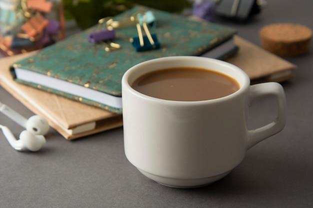 Table de travail avec cahiers, fournitures de bureau et tasse à café. fond gris. espace de travail.