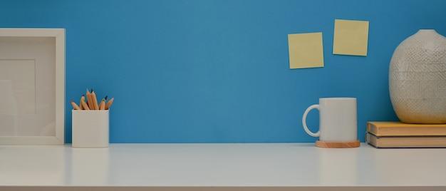 Table de travail avec copie espace papeterie et décorations sur un bureau blanc avec mur bleu