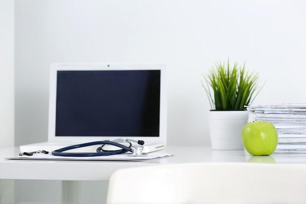 Table de travail du docteur en médecine. ordinateur portable, papiers, pomme verte et stéthoscope allongé sur la table au bureau du médecin. concept de soins de santé et médical