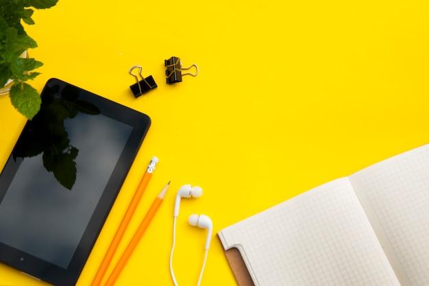 Table de travail avec écran ipad, cahier ouvert et feuilles vertes. fond jaune . vue de dessus.