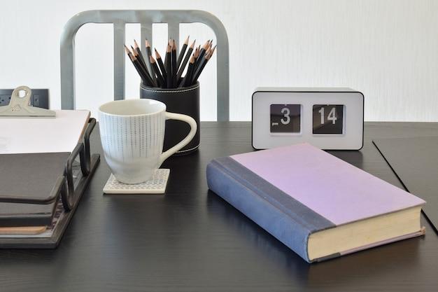 Table de travail avec livre, crayons, tasse de café et horloge dans une maison