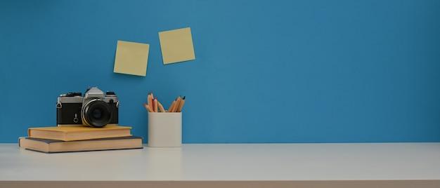 Table de travail avec des livres de l'appareil photo et de la papeterie de l'espace sur un bureau blanc avec mur bleu