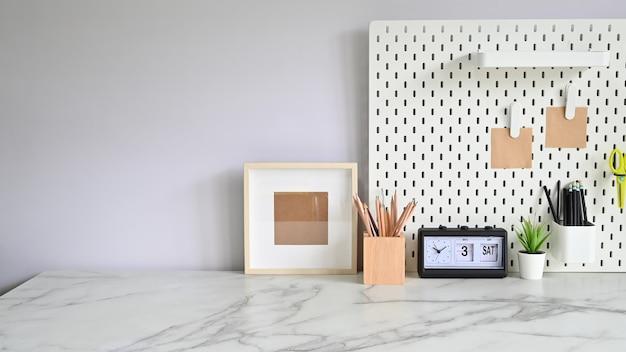 Table de travail en marbre avec crayons, cadre photo avec panneau d'affichage et plante d'intérieur.