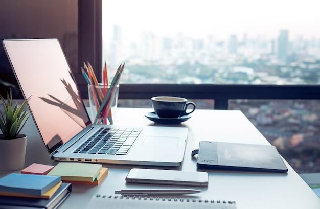 Table de travail moderne avec ordinateur portable et vue sur les paysages urbains depuis la fenêtre