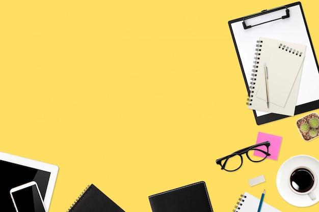 Table de travail plate avec ordinateur portable, fournitures de bureau, tasse à café, tablette et téléphone portable sur pastel jaune