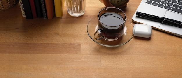 Table de travail rustique avec espace copie, tasse à café, ordinateur portable, livres et décorations sur un bureau en bois