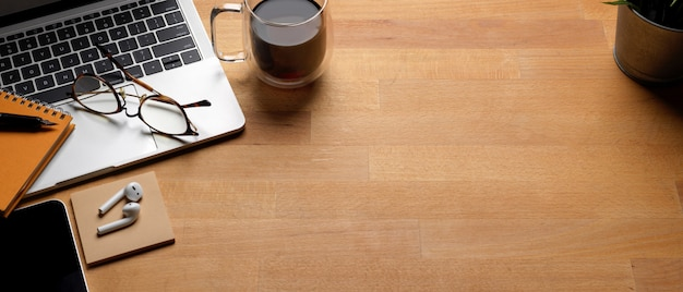 Table de travail tendance avec espace copie, ordinateur portable, tasse à café et fournitures sur un bureau en bois