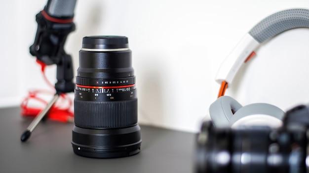 Table avec des trucs de créateur de contenu. appareil photo, microphone, objectif de l'appareil photo et écouteurs. travailler à domicile