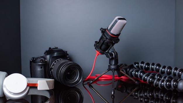 Table avec des trucs de créateur de contenu. appareil photo, microphone, trépied et écouteurs. travailler à domicile