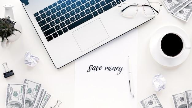 Table avec des trucs de travail des finances. ordinateur portable, argent, café, stylo, papiers