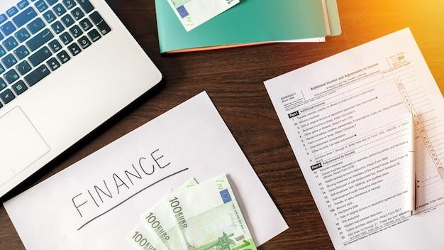 Table avec des trucs de travail des finances. ordinateur portable, argent, stylo, papiers