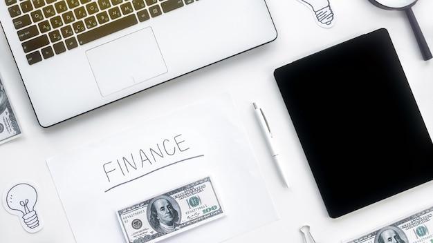 Table avec des trucs de travail des finances. ordinateur portable, argent, tablette, stylo, papiers