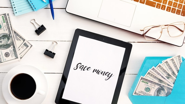 Table avec des trucs de travail des finances. ordinateur portable, café, argent, tablette, stylo, papiers