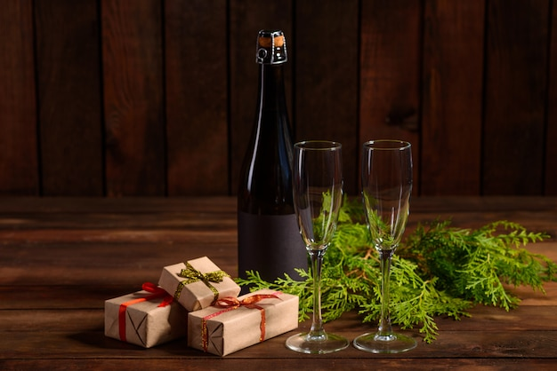 Table de vacances de noël avec des lunettes et une bouteille et des cadeaux