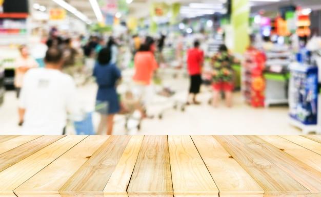 Table vide en bois à l'avant avec une foule floue et anonyme en attente de paiement à la caisse.
