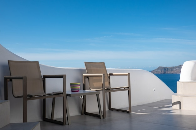 Table vide et une chaise avec un ciel bleu à l'île de santorin, grèce