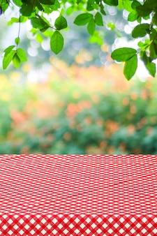 Table vide avec nappe rouge sur jardin flou et fond de bokeh