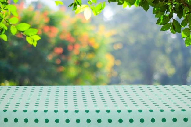Table vide avec une nappe verte à pois sur parc flou avec bokeh