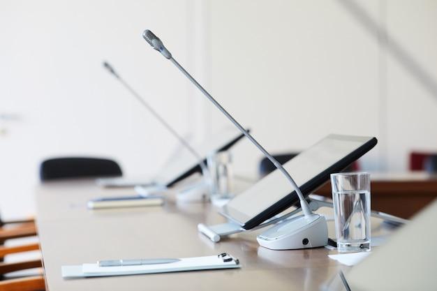 Table vide avec ordinateur et microphone dans la salle de conférence