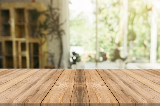 Table vide de planche de bois en face de l'arrière-plan flou. perspective bois brun sur le flou dans un café - peut être utilisé pour l'affichage ou le montage de vos produits.mock up pour l'affichage du produit.