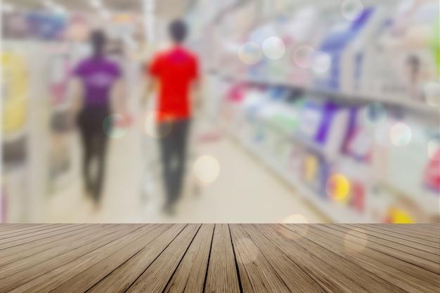 Table vide de planche de bois en face de l'arrière-plan flou. perspective bois clair sur le flou dans un supermarché - peut être utilisé pour l'affichage ou le montage de vos produits. maquette pour l'affichage du produit.