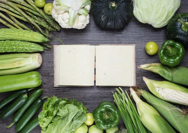 Table avec un vieux livre et de légumes verts